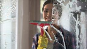 A boa esposa com as janelas de limpeza da casa do prazer e da sala de lavagem, pede em casa foto de stock