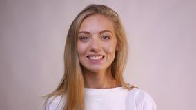 Boa menina caucasiano de sorriso com o cabelo longo louro que olha reto e posição no fundo branco vídeos de arquivo