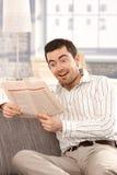 Boa notícia da leitura masculina nova em casa que sorri imagem de stock royalty free