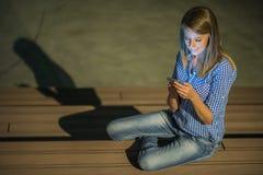 Boa notícia A moça bonita verifica algo em seu telefone esperto e sorri distraìdamente Foto de Stock