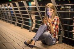Boa notícia Texting de sorriso da mulher feliz nova em seu telefone Foto de Stock