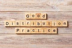 Boa palavra da prática da distribuição escrita no bloco de madeira bom texto na tabela, conceito da prática da distribuição foto de stock