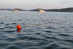 Boa rossa con le barche nel fondo Fotografia Stock