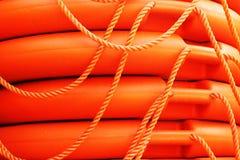 Boa rotonda impilata di salvataggio arancio, salvavita del marinaio del mare. Immagine Stock