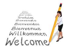 Boa vinda da escrita da mulher de negócios em várias línguas fotos de stock royalty free