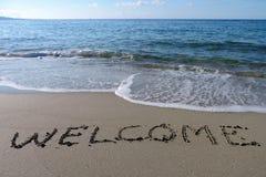 Boa vinda da inscrição na areia molhada Imagens de Stock