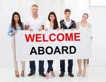 Boa vinda da terra arrendada do grupo de pessoas a bordo do cartaz fotografia de stock