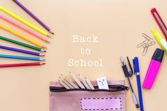 A boa vinda de volta ao fundo da escola, o lápis colorido da cor e os artigos de papelaria ensacam em fundos amarelos com espaço  Imagem de Stock Royalty Free