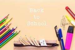 A boa vinda de volta ao fundo da escola, o lápis colorido da cor e os artigos de papelaria ensacam em fundos amarelos com espaço  Imagens de Stock