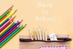 A boa vinda de volta ao fundo da escola, o lápis colorido da cor e os artigos de papelaria ensacam em fundos amarelos com espaço  Fotografia de Stock