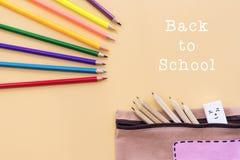 A boa vinda de volta ao fundo da escola, o lápis colorido da cor e os artigos de papelaria ensacam em fundos amarelos com espaço  Imagens de Stock Royalty Free