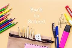 A boa vinda de volta ao fundo da escola, o lápis colorido da cor e os artigos de papelaria ensacam em fundos amarelos com espaço  Fotos de Stock