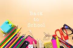 A boa vinda de volta ao fundo da escola, o lápis colorido da cor e os artigos de papelaria ensacam em fundos amarelos com espaço  Foto de Stock Royalty Free