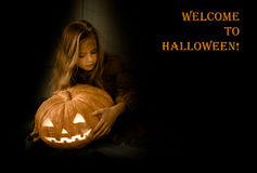 Boa vinda a Dia das Bruxas menina com abóbora de incandescência em um fundo preto Foto de Stock Royalty Free