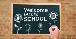 Boa vinda do desenho da mão de volta ao texto e às flores de escola no quadro-negro imagens de stock royalty free