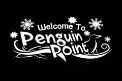 Boa vinda iluminada ao sinal do ponto do pinguim no fundo preto em jardins de Busch imagem de stock royalty free