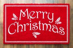 Boa vinda Mat On Wood Floor Background do vermelho do Feliz Natal imagem de stock royalty free