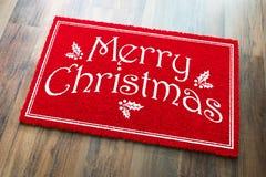 Boa vinda Mat On Wood Floor Background do vermelho do Feliz Natal imagem de stock
