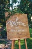 Boa vinda a nossa celebra??o Placa escrita à mão do sinal do texto da caligrafia no painel de madeira no jardim com galho da árvo foto de stock