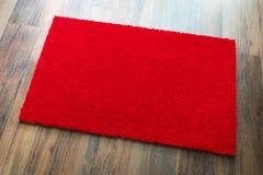 Boa vinda vazia Mat On Wood Floor Background do vermelho pronto para seu texto imagens de stock royalty free