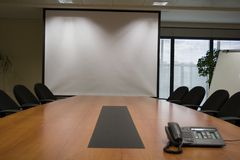 Board. A straight on view of a conference table; with conference phone in the middle; chairs; and a blank whiteboard.; Crop is vertical Stock Image