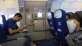 On board of airplane. TUNISIA, SOUSSE, JULY 15, 2010: People aboard an airplane. Seating near emergency exit, Tunisia, July 15, 2010 stock video footage