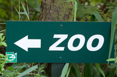Board with arrow sign pointing direction to the Zoo Stock Photos