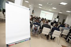 Board on background of audience in conference room. Business concept stock image