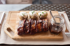 Board of barbecue ribs and potatoe on wooden Stock Photography