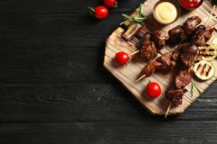 Board with barbecued meat, garnish and sauces on wooden background, top view royalty free stock photography