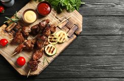 Board with barbecued meat, garnish and sauces on wooden background, top view. Space for text royalty free stock photo