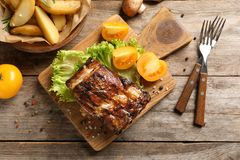 Board with barbecued ribs and garnish on wooden background stock image