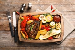 Board with barbecued steak, garnish and sauce on wooden background. Top view stock photo