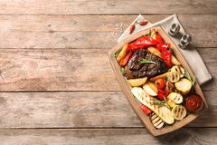 Board with barbecued steak, garnish and sauce on wooden background, top view royalty free stock photo