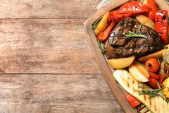 Board with barbecued steak and garnish on wooden background, top view royalty free stock photo