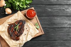 Board with barbecued steak and sauce on wooden background, top view. royalty free stock image