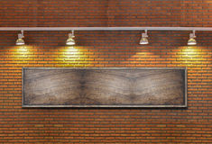 Board on a brick wall with light. Royalty Free Stock Photo