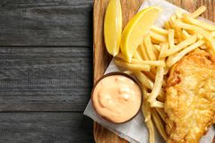 Board with British traditional fish and potato chips on wooden background, top view. Space for text royalty free stock images