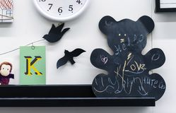 "Board for chalk in the form of bear. The inscriptions on the board are ""Love"", ""Hello"" in English and ""Smile"" in stock photography"