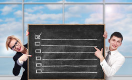 Board with check box. Businesspeople in office holding chalk board with check box Stock Images