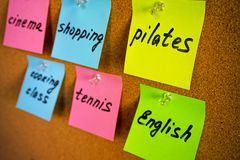 Board with colorful stickers about activities and hobbies: pilates English shopping tennis cooking class cinema and pins stock images