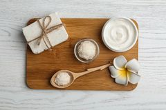 Board with cosmetic products and Shea butter on table stock images