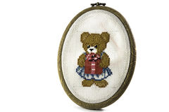 Board embroidery which left a teddy bear on a white background isolated Stock Photos