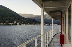 On board the ferry and leaving behind the port of Sami Kefalonia. Ferry railing and in the distance the port of Sami and its mountains in Kefalonia towards Stock Photography