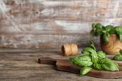 Board with fresh basil leaves on wooden table. Space for text stock photography