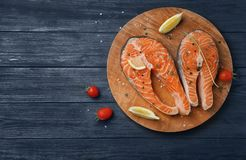 Board with fresh raw salmon steaks and seasonings. On wooden background, top view Royalty Free Stock Photography