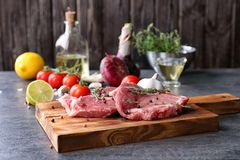 Board with fresh raw steaks and thyme. On table Royalty Free Stock Images