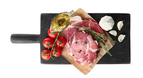 Board with fresh raw steaks, thyme and vegetables. Isolated on white Royalty Free Stock Image