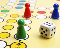Board game and dice. A board game with colorful pieces and a dice stock images
