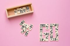 Board game of dominoes GO on a pink background stock photo